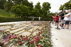 访客在Kennedys gravesite的位置花 免版税库存图片