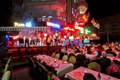 访客手表晚场演出在餐馆 图库摄影