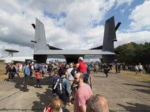 访客排队观看美国空军队的白鹭的羽毛CV-22的货物区域 库存照片