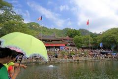 访问生活池塘的旅游举行伞 库存照片