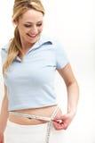 评定她的腰部的兴高采烈的妇女 免版税图库摄影