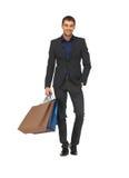 诉讼的英俊的人与购物袋 免版税库存图片
