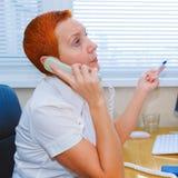 诊所的妇女医生 一位年轻医生在一家现代医院接从一名患者的一个电话 库存照片