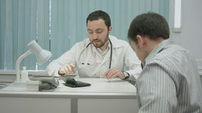 诊所的男性有胡子的医生计算高价 股票录像