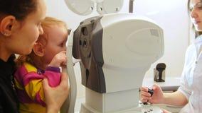 诊所的验光师检查小女孩` s视觉-儿童` s眼科学的 影视素材