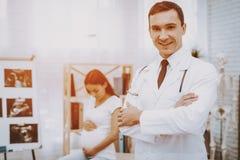 诊所 医生摆在 孕妇 腹部 免版税库存图片