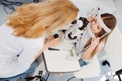 诊断她的患者的精确美妙的医生 免版税库存图片