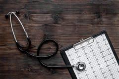 诊断心脏病 心电图,在黑暗的木背景顶视图copyspace的听诊器 免版税库存照片