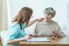 诊断老妇人的医生 免版税库存图片