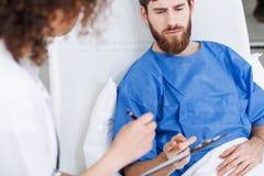 诊断年轻人的精神病学的医生 库存照片