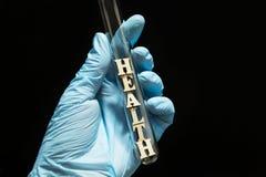 词'健康'在玻璃试管在一位医生的手上医疗手套的在黑背景,概念 免版税库存照片