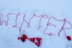 词冬天在与一条羊毛制红色螺纹的雪被写 美丽的概念礼服女孩纵向佩带的空白冬天 户外 免版税库存图片