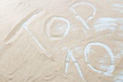 词名列前茅10在海滩的金黄沙子被写由海 概念-十个最佳的海滩、游览或者方式放松在t 库存照片