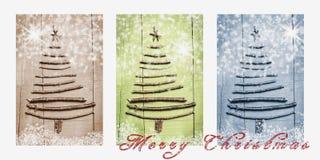 词在多雪的三张相联写的圣诞快乐在褐色、绿色和蓝色 圣诞树由木分支做成 免版税库存图片
