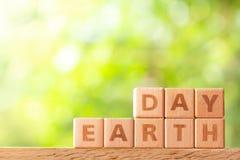 词在木桌上的木块写的地球日 库存照片