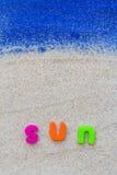 词太阳被放置的沙子蓝色板 免版税库存照片