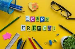词学会用被雕刻的信件做的法语在有办公室或学校用品的,文具黄色书桌 Franch的概念 库存图片