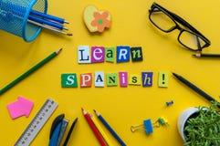 词学会用被雕刻的信件做的西班牙语在有办公室或学校用品的,文具黄色书桌 概念  免版税库存照片