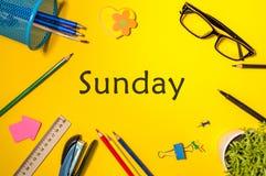 词星期天顶视图和在黄色桌背景的不同的办公用品 工作天的企业概念 免版税库存图片