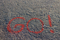 词是!写在沥青,地面 白垩的红颜色 免版税库存照片
