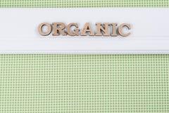 词有机与抽象木信件 在绿色纹理的背景白色盘区 免版税库存图片