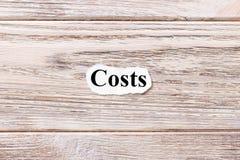 词的费用在纸的 概念 费用的词在木背景的 免版税库存照片