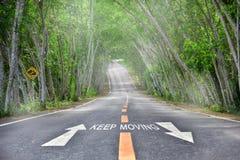 词的继续移动与在路的白色箭头 库存图片