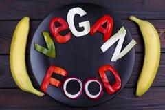 词素食主义者食物雕刻了在黑色的盘子,舱内甲板位置的菜 免版税库存图片