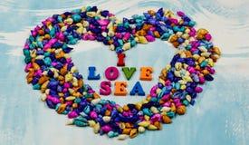 词组`我爱海`,被张贴了在小五颜六色的壳里面的心脏在蓝色背景的 库存图片