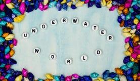 词组`水下的世界`,被张贴了在蓝色背景的小五颜六色的壳框架里 库存照片