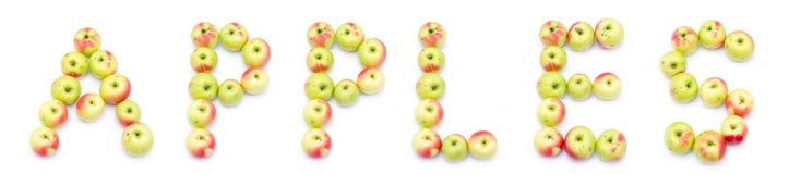 词苹果拼写了在yelloe绿色红色新鲜的苹果外面  免版税图库摄影