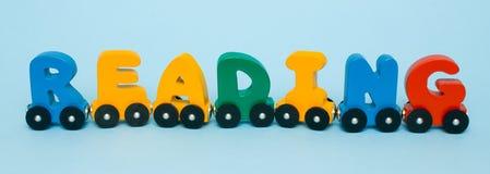 词读书由信件火车字母表制成 红色黄绿色和蓝色的明亮的颜色在白色背景 幼儿期dev 库存照片