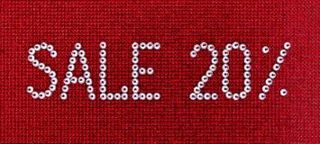 词销售在红色帆布后面被做假钻石水晶颜色 免版税库存图片