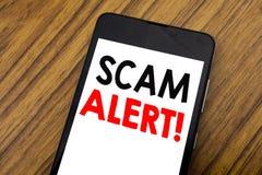 词,写手写诈欺戒备 在手机手机写的欺骗警告的企业概念,木背景与 库存图片