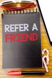 词,写提到一个朋友 在笔记本书写的推举行销的,与稠粘的木背景企业概念 库存图片