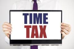 词,写时间税 征税在片剂膝上型计算机写的财务提示的企业概念举行由人弄脏了backgro 免版税库存图片