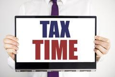 词,写税时间 征税在片剂膝上型计算机写的财务提示的企业概念举行由人弄脏了backgro 免版税图库摄影