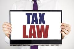 词,写税法 征税在片剂膝上型计算机写的税收规则的企业概念举行由人弄脏了背景 Bu 免版税库存图片
