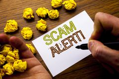 词,写诈欺戒备 在笔记本在木背景的便条纸写的欺骗警告的概念与被折叠的纸手段 免版税库存图片