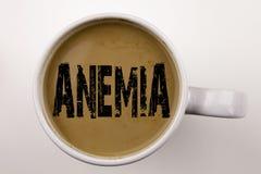 词,写贫血症文本在杯子的咖啡 医疗诊断铁缺乏症的企业概念发育不全在白色背景wi 免版税图库摄影
