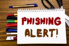 词,写Phishing戒备 在笔记本写的欺骗警告危险的企业概念,与办公室equipme的木背景 免版税库存照片