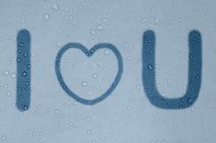 词组我爱你在一个有雾的蓝色窗口 图库摄影