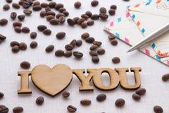 词`我爱你`,信封,笔,溢出了在白色背景的咖啡 免版税库存照片