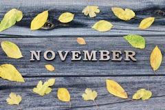 词11月,木信件 黄色叶子框架,木背景 免版税库存图片