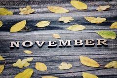 词11月,木信件 黄色叶子框架,木背景 库存图片