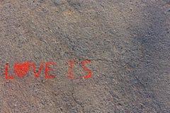 词组爱在沥青,地面被写 白垩的红颜色 免版税库存图片