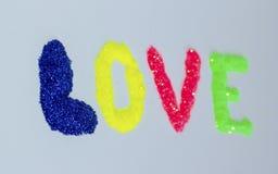 词`爱`的题字由宽松闪烁制成在轻的背景 免版税库存照片