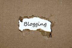 词blogging出现在被撕毁的纸后 免版税库存照片