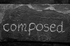 词COMPOSED写与白垩在黑石头 库存照片