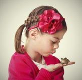 亲吻青蛙的逗人喜爱的矮小的公主 免版税库存照片